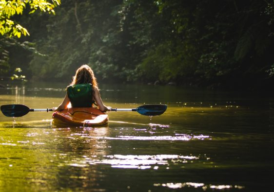 woman on kayak on body of water holding paddle